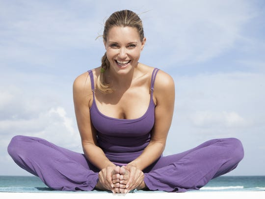 Young woman doing yoga exercise on beach.