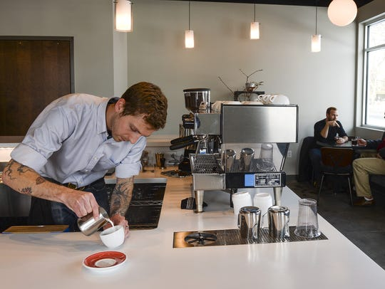 Jonathan Jarrow, owner of Harbinger Coffee, pours a