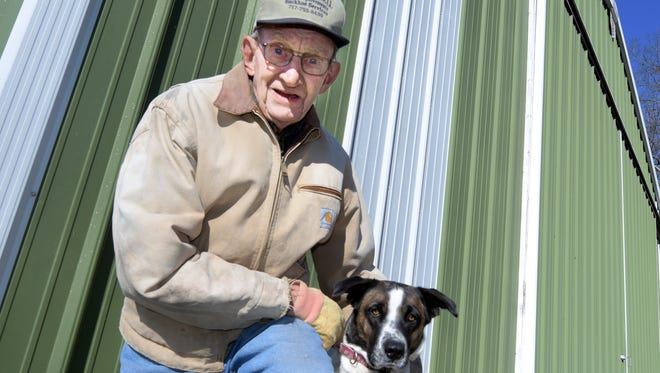 Tuesday, Jan. 19, 2016--Marlyn Miller is joined by his son's dog, Dotty, outside the pole building which held the 2002 Kawasaki Mule the pair used to get them around his farm. The vehicle was stolen on Christmas Eve.