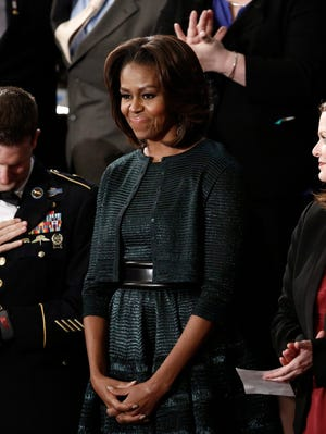First lady Michelle Obama, flanked by special guests, wore a dress by Azzedine Alaia to the State of the Union address Tuesday night.
