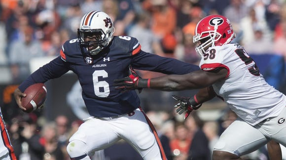 Auburn Tigers quarterback Jeremy Johnson stiff arms Georgia defensive lineman Billy Seward.