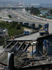 Workers demolish a section of Highway 580 in Oakland,