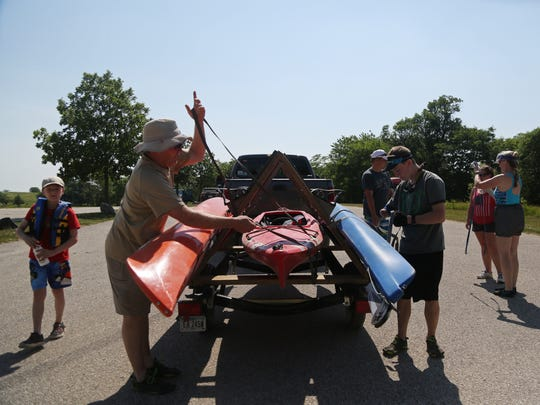 Eric Hart and his 13-year-old son Jarod Hart unfasten kayaks from their trailer before a kayaking trip down the Raccoon River with their family on Sunday, June 11, 2017, near Coon Rapids. Avid adventure racers, Eric and Jarod spent the weekend biking and kayaking with their family.