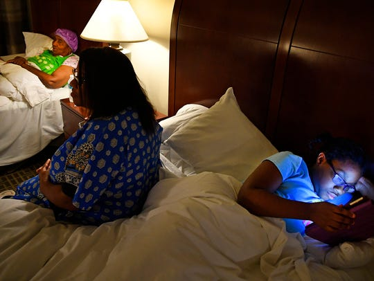 Imana Malbroue, 10, looks at her mother's iPad as she,