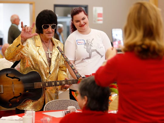 Rebecca Shoemake has her photo taken by Carla McCall, both volunteers, with a man dressed as Elvis during the annual Christmas Dinner for Those Alone at First and Calvary Presbyterian Church on Sunday, Dec. 25, 2016.