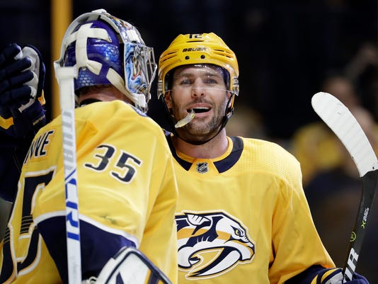Nashville Predators center Mike Fisher, right, celebrates with goalie Pekka Rinne (35), of Finland, after beating the Anaheim Ducks in an NHL hockey game Thursday, March 8, 2018, in Nashville, Tenn. The Predators won 4-2 for their tenth consecutive win. (AP Photo/Mark Humphrey)