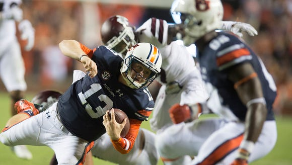 Auburn quarterback Sean White (13) falls during a run