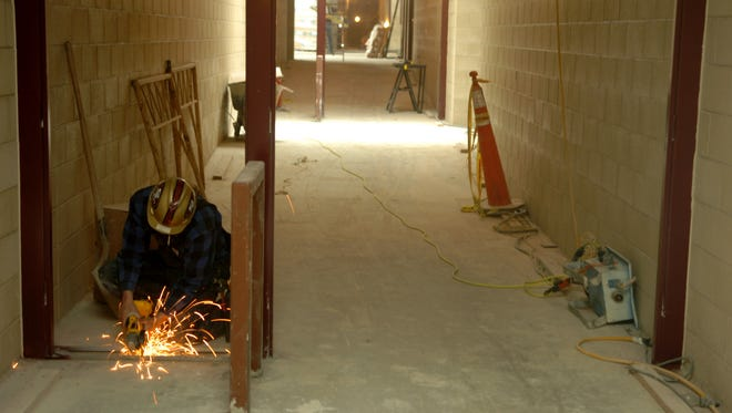 A worker saws through metal at the Cold Springs Middle School when it was being built in 2006.