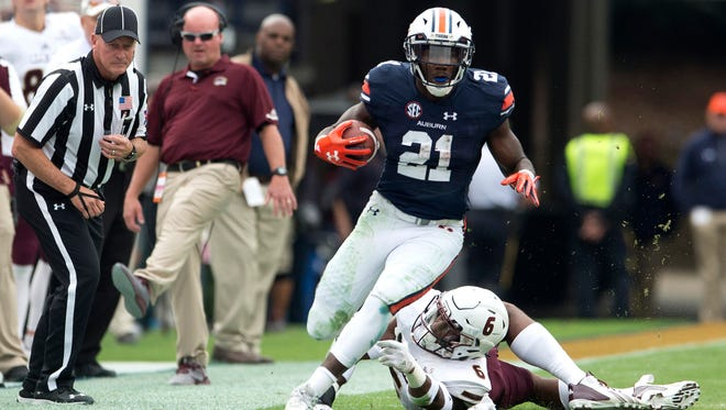 Auburn running back Kerryon Johnson (21) breaks a tackle attempt by Louisiana Monroe safety Wesley Thompson (6) during the NCAA football game between Auburn and Louisiana Monroe on Saturday, Nov. 18, 2017, in Auburn, Ala.