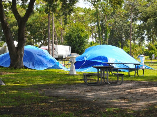 Blue tarps cover some tents alongside recreational