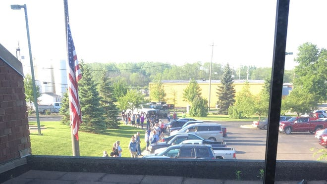 Office Manager Bonnie Alfred captures a long line stretched out the door of a Bureau of Motor Vehicles office in Wooster on the early morning of May 26, the day Ohio's BMV stations began reopening.