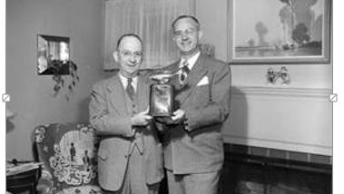 Rotary Club Secretary Lee Bouldin, left, and Rotarian Dr. Durward Hall display the Dr. Wallis Smith Memorial Trophy that would go to the Rotary Club member catching the largest game fish from an Ozarks stream or lake between April and July 1, 1951.