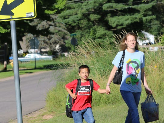 Shay Zarda, a third grader, and Whitney Peterson walk to  Madison Elementary School on the first day of classes.