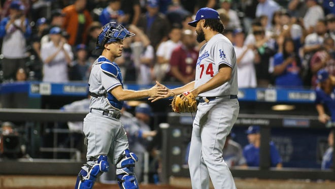 Los Angeles Dodgers catcher Austin Barnes (15) celebrates with pitcher Kenley Jansen (74) after defeating the New York Mets.