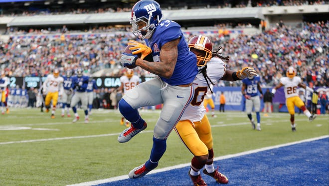 New York Giants wide receiver Odell Beckham Jr. (13) comes down with a catch for a touchdown against Washington Redskins free safety E.J. Biggers (30) during the first quarter of an NFL football game, Sunday, Dec. 14, 2014, in East Rutherford, N.J. (AP Photo/Julio Cortez)