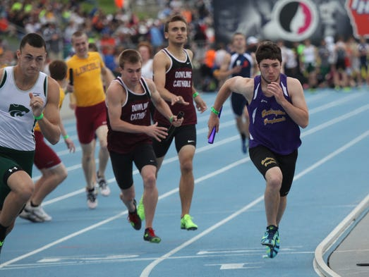 Dowling Catholic's Spencer Clark takes the baton from Joe Gorsche in the 4x800 relay Thursday at the Class 4-A co-ed state track meet at Drake Stadium in Des Moines. They were joined by Ian McKenzie and Mike McManus to finish 14th in a time of 8:06.92. May 22, 2014