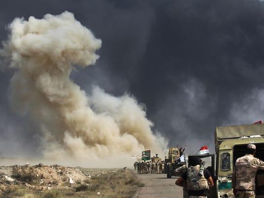 Smoke billows as Iraqi forces advance toward the Islamic