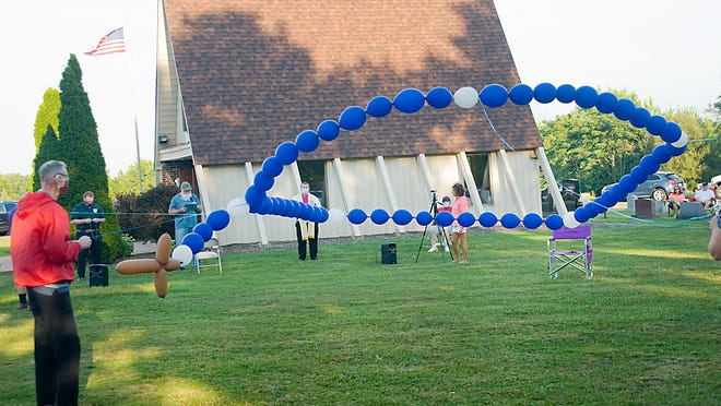 A helium balloon rosary is secured on a windy Saturday evening at St. Joseph Cemetery in Alliance. Parishioners gathered to recite the rosary in tribute to the United States.