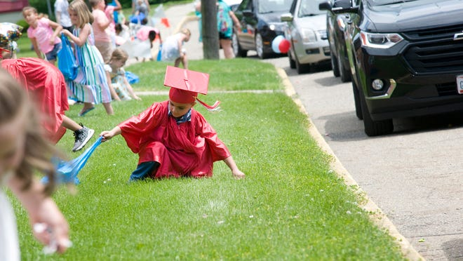 Armando Hinojosa, 6, gathers candy during a parade celebrating graduation at the Alliance Early Learning School Sunday, June 7, 2020.