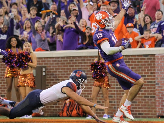 Clemson safety Tanner Muse runs past Syracuse quarterback