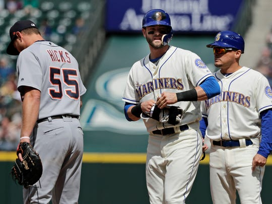 Seattle Mariners' Mitch Haniger, center, stands on