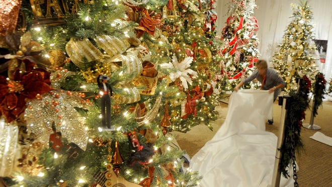 """Rhonda Kaihara, a volunteer at the Ronald Reagan Presidential Library & Museum in Simi Valley, places a white cloth around trees in the """"Christmas Around the World"""" exhibit."""