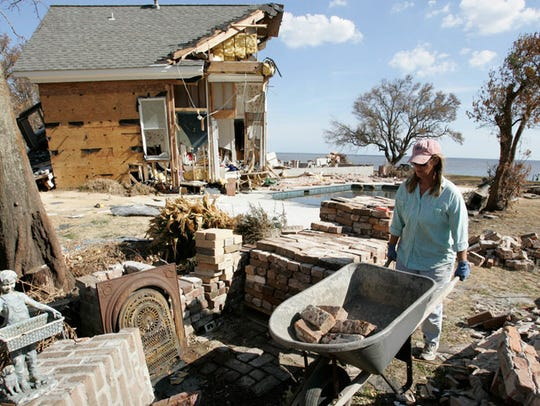 Cindy Frank cleans up debris from her father's house,