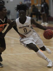 Madison County's Travis Jay dribbles up court during