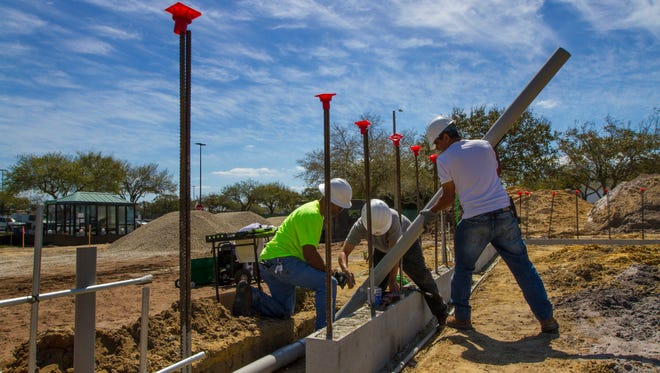 Technicians with Collier Electric of Fort Myers install a conduit pipe into a commercial parcel being built at Coralwood Shopping Center in Cape Coral.