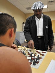 Chess teacher and motivational speaker Eugene Brown plays Doua Vang Monday morning at NTC Alternative High School.