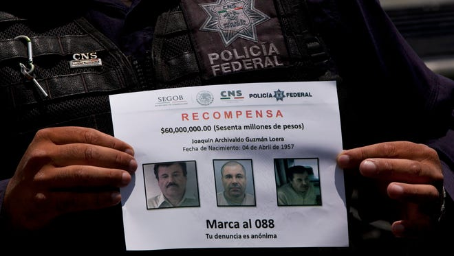 """FILE - In this July 16, 2015 file photo, a Federal Police shows a reward notice for information leading to the capture of drug lord Joaquin """"El Chapo"""" Guzman, who made his escape from the Altiplano maximum security prison via an underground tunnel,  in Almoloya, west of Mexico City. Mexican President Enrique Pena Nieto posted on his Twitter account, Friday, Jan. 8, 2016, that drug lord Joaquin 'Chapo' Guzman has been recaptured.(AP Photo/Marco Ugarte, File)"""