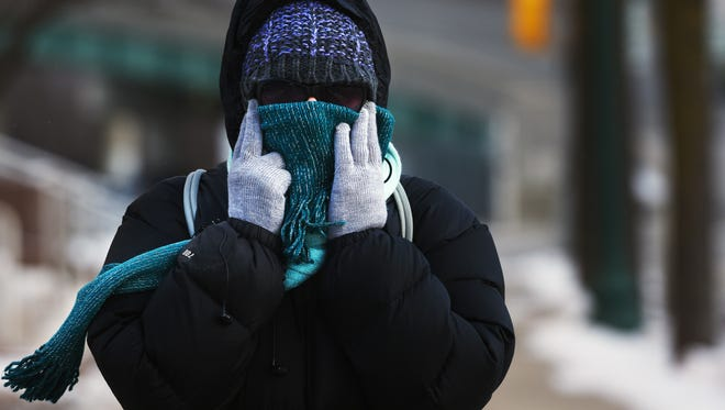 Malania Hill dons glasses, hat, scarf and gloves to keep her skin from being exposed to the extremely cold temperatures as she walks along 11th Street in downtown Sioux Falls on Thursday afternoon.