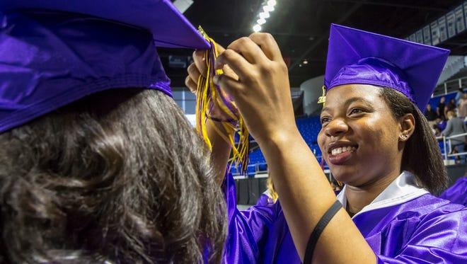 Tianna Johnson helps Jordan Ashby get her tassel in order at the 2018 Smyrna High School graduation  held at MTSU Friday, May 18, 2018.