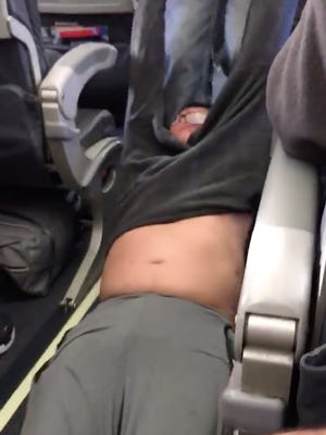Screen shot from a video of a man being dragged off of a United Airlines' plane before it left Chicago and headed to Louisville.