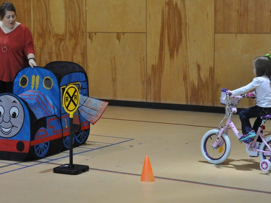 Alison Byram, assistant director of First United Methodist Preschool & Childcare, teaches students to stop for trains when riding their bikes.