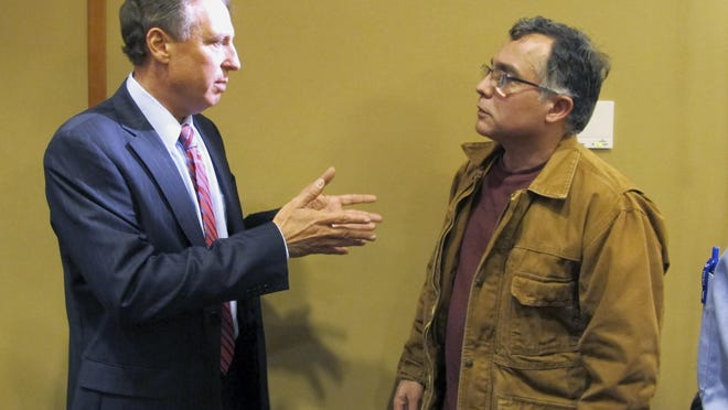 Michael Goldberg, left, federal receiver appointed to run two Vermont ski resorts amid fraud allegations, speaks to investor Felipe Vieira on April 27 in Jay.