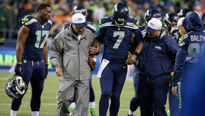 Seattle Seahawks quarterback Tarvaris Jackson (7) is helped off the field after going down with an injury during the second half of a preseason NFL football game against the Denver Broncos, Friday, Aug. 14, 2015, in Seattle.