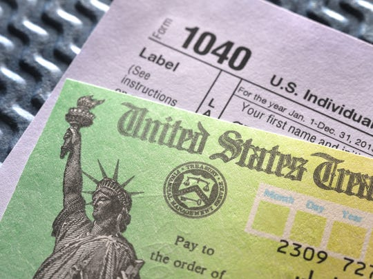 Tax Form 1040 and a refund check