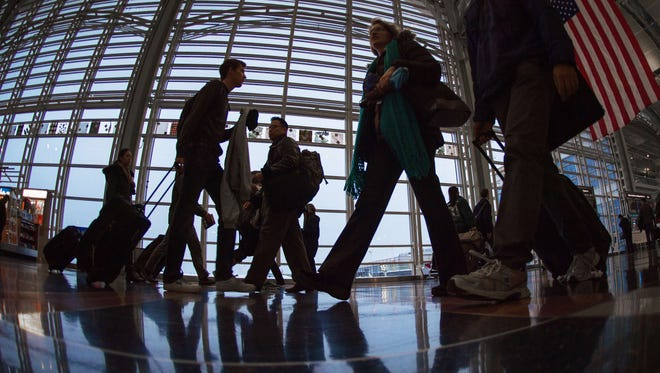 This file photo from Nov. 26, 2014, shows airline travelers at Ronald Reagan National Airport.