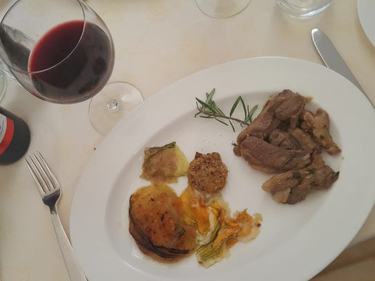 Stewed lamb with onion and zucchini flowers and a bottle