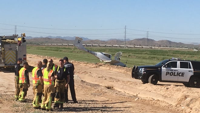 Fire crews stand near the wrecked plane in Goodyear, waiting for the FAA to arrive and investigate.