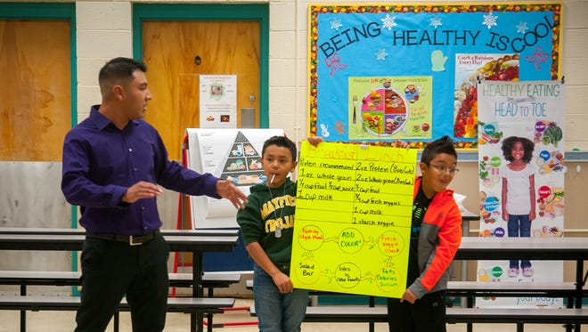 Head Start Parent Policy Council vice president Gabriel Duran, left, points out the benefits of a well-balanced diet with the help of 9-year-olds Elijah Duran and Dante Acosta during a Head Start Healthy Eating Workshop at Mesilla Park Elementary School on Dec. 16.