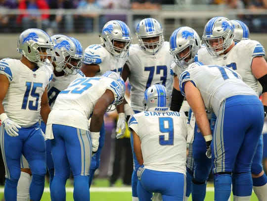 The Detroit Lions huddle around Matthew Stafford in