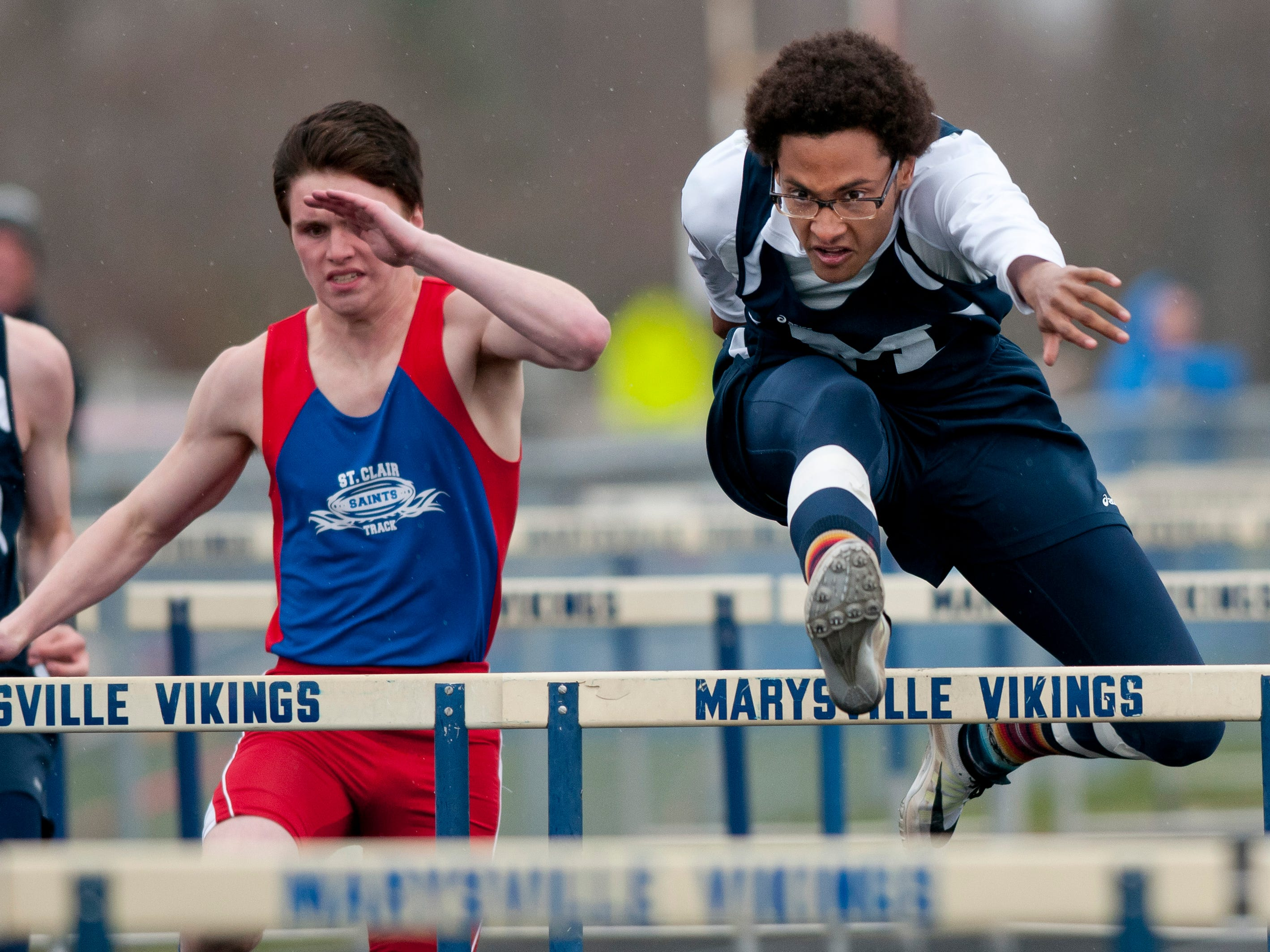 Marysville senior Dylan Pankow and St. Clair senior Nathan Roberts compete in the hurdles during a track meet Thursday, April 30, 2015 at Marysville High School.