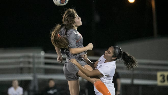Lely's Emily Hamilton heads the ball over Mariner's Julissa Chimelis in the Region 3A-4 girls soccer quarterfinal game on Tuesday, Feb. 6, 2018, in Cape Coral.