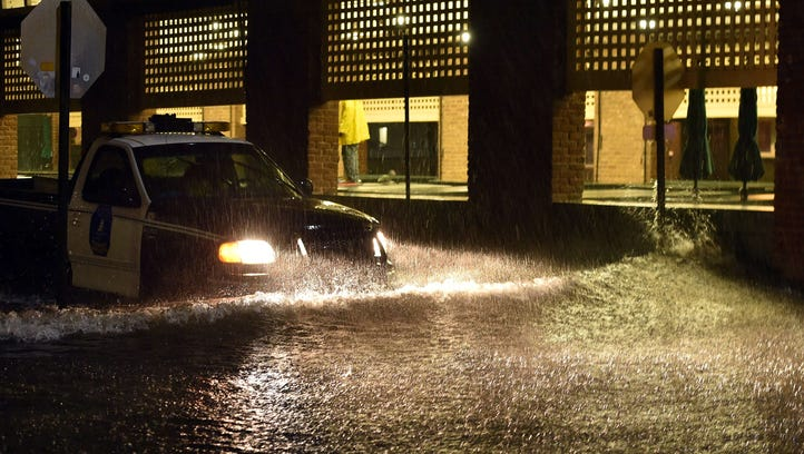 A police car makes its way on a flooded street in downtown