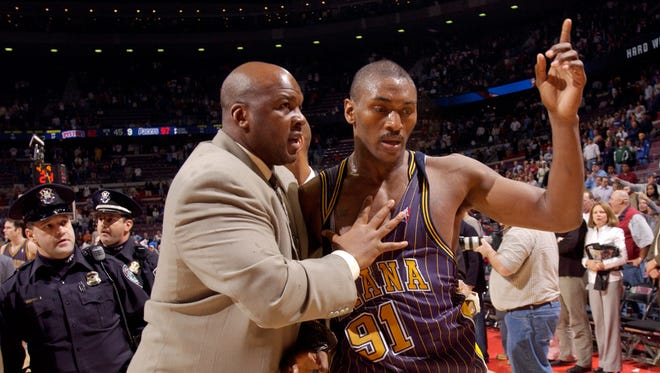 FILE -- Indiana Pacers' Ron Artest is led off the court by Pacers special consultant Chuck Person after a brawl near the end of the game against the Detroit Pistons in Auburn Hills, Mich., in this Nov. 19, 2004 photo.