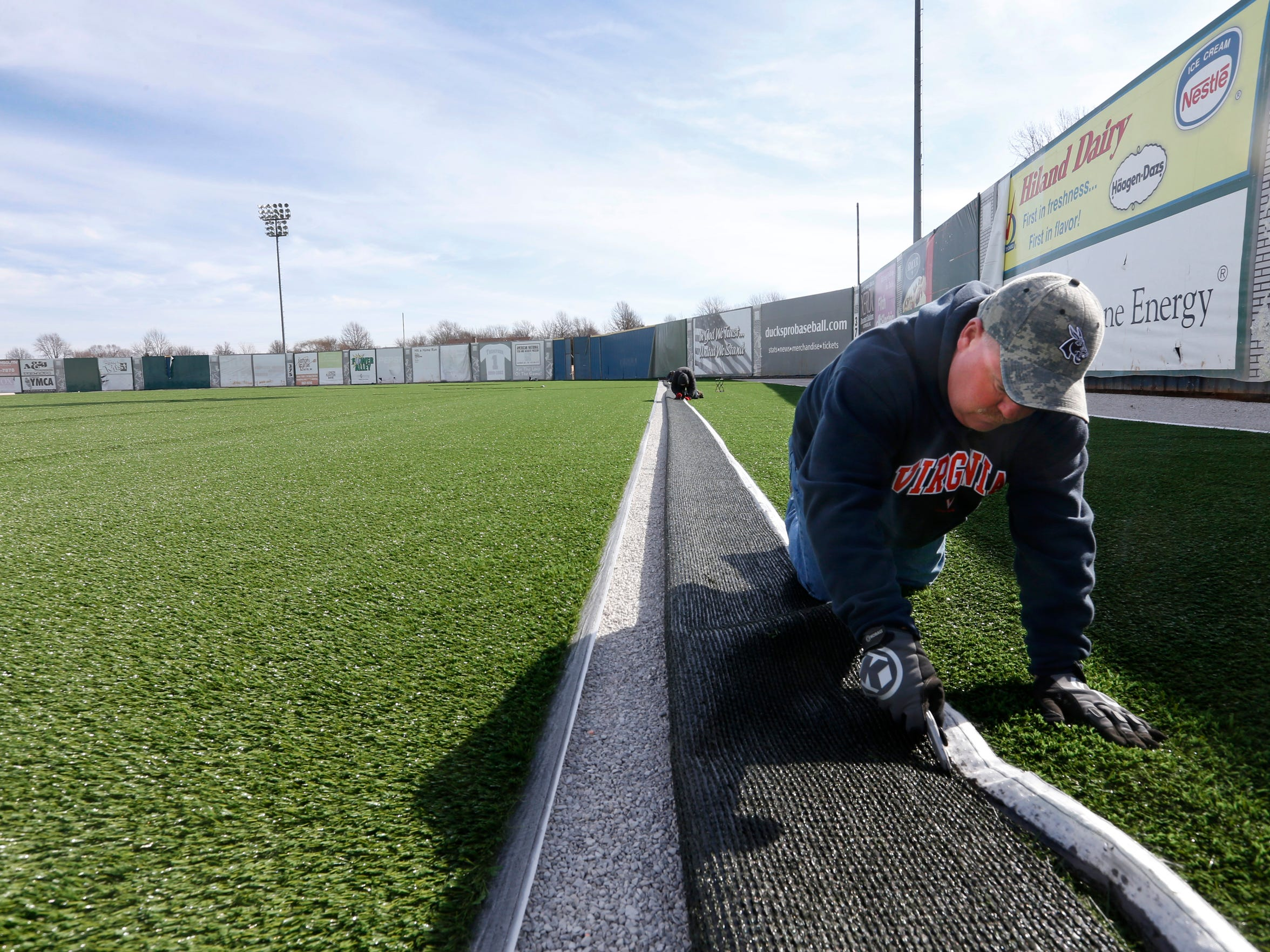Andy Dalton, of Sports Construction Management, cuts the trim off of a sheet of artificial turf while installing the new field at Duck's Stadium in Ozark on Thursday, Feb. 18, 2016.