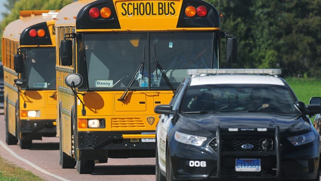 A law enforcement officer leads two school buses after a shooting that injured Harrisburg High School principal Kevin Lein on Wednesday.