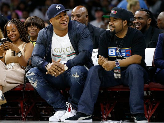 LL Cool J, second from front left, and Ice Cube watch the action as The Power plays the Ghost Ballers during the first half of Game 1 in the BIG3 Basketball League in Philadelphia, Pa., Sunday, July 16, 2017. (AP Photo/Rich Schultz)